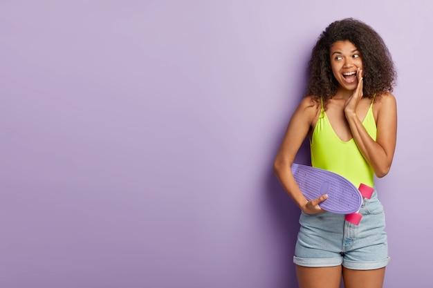 幸せな女性スケーターは娯楽中に好きな趣味を楽しんで、ロングボードを保持します