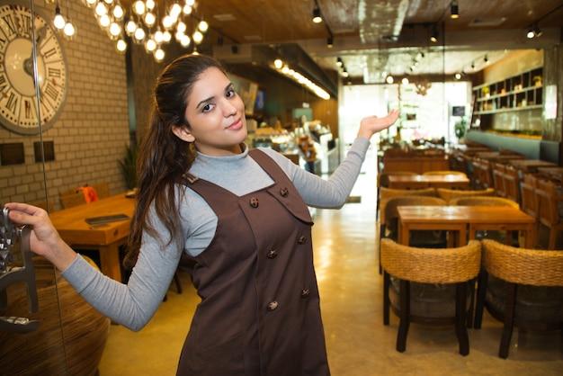 그녀의 카페를 보여주는 행복 여성 중소 기업 소유자