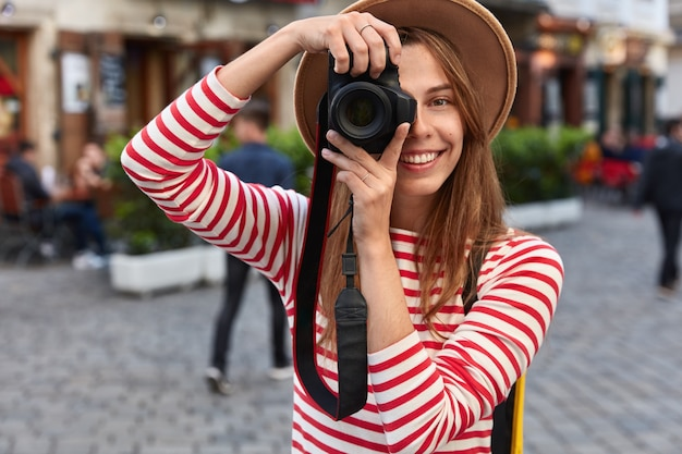 Happy female spends free time on hobby, takes picture of city street on camera during leisure