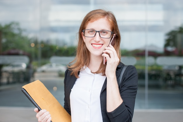 Happy female student calling on phone outdoors