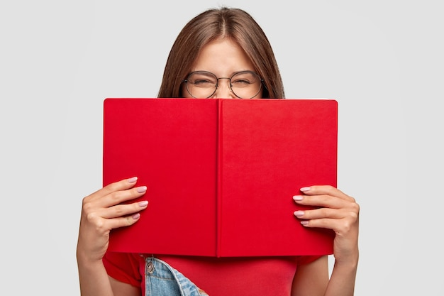 Happy female student laughs positively, wears round spectacles, hides behind red book, smiles as read something funny, poses against white wall. people, youth, education and reading concept