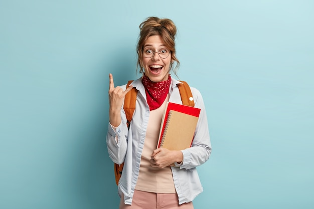 Happy female student with combed hair, makes rock n roll gesture, has glad expression, rejoices finishing of studying year