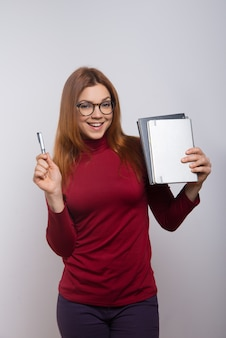 Happy female student with textbooks and pen