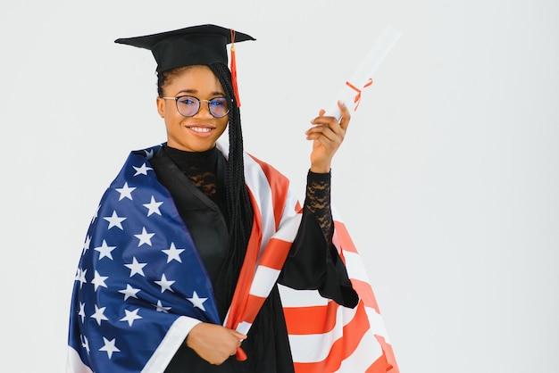 アメリカの国旗を持つ幸せな女子学生。アメリカで勉強する概念