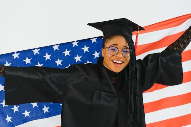 アメリカの国旗の壁で幸せな女子学生。アメリカで勉強する概念