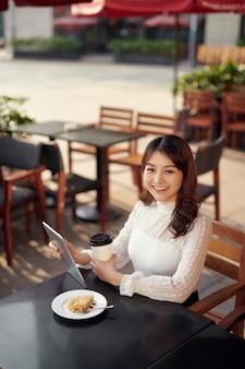 Счастливая студентка работает на цифровом планшете и расслабляется в кафе
