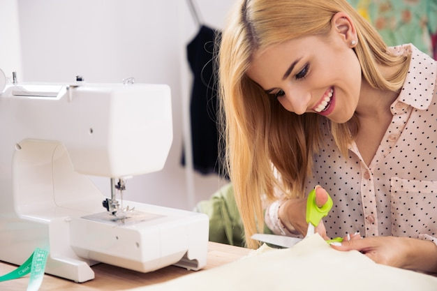 Happy female tailor cutting cloth