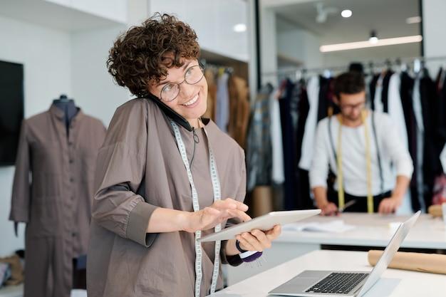 Счастливая женщина-портной с тачпадом и смартфоном консультирует клиентов или принимает заказы по телефону и онлайн
