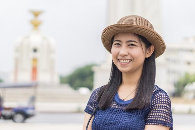 Счастливая женщина фотографирует в бангкоке памятник демократии - концепция радостного путешествия
