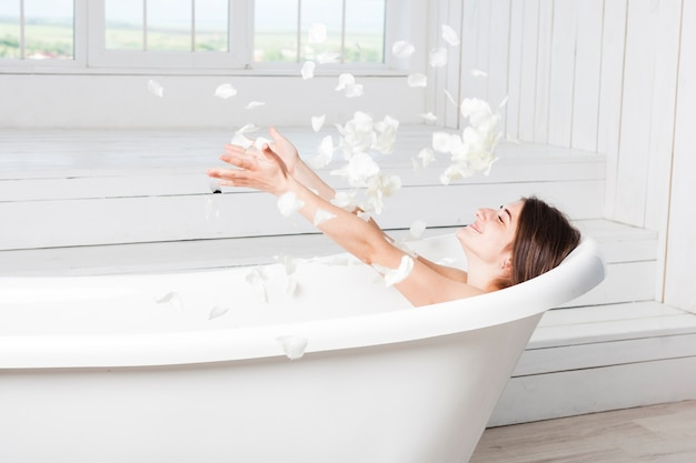 Happy female throwing petals lying in bathtub