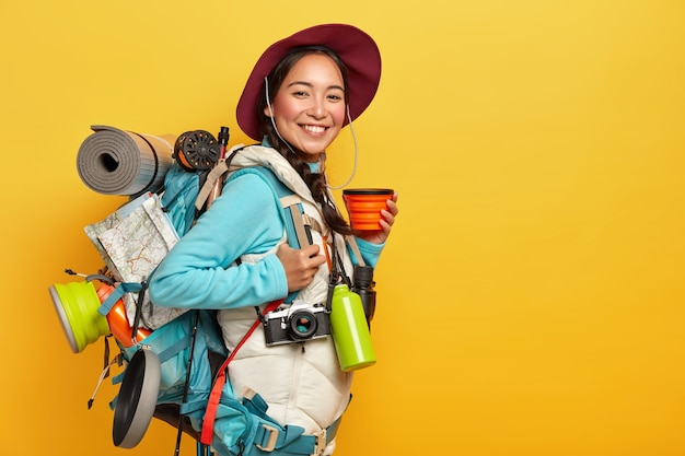 Happy female tourist drinks coffee or tea, poses with backpack, rolled sleeping rag, wears hat, jumper and vest, stops during journey, isolated over yellow wall