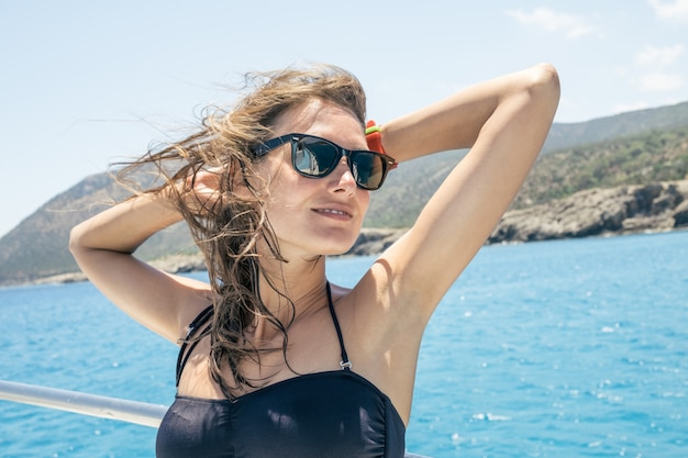 Happy female tourist having fun on sailboat