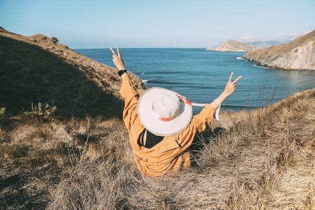 平和を象徴する彼女の手を座って上げる夏の帽子をかぶって幸せな女性観光客
