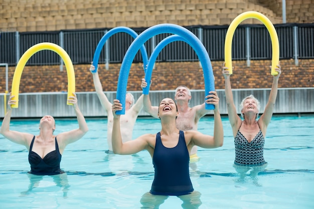 Happy female trainer and senior swimmers exercising with pool noodle
