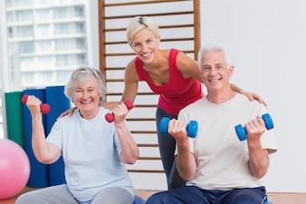 Happy female trainer with senior couple