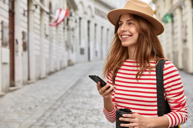 Happy female travel blogger uses route application, holds modern smart phone device, walks across ancient city, drinks takeaway coffee
