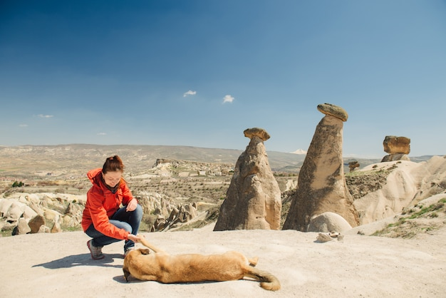 Happy female traveler bonding with local dog on fairy chimneys