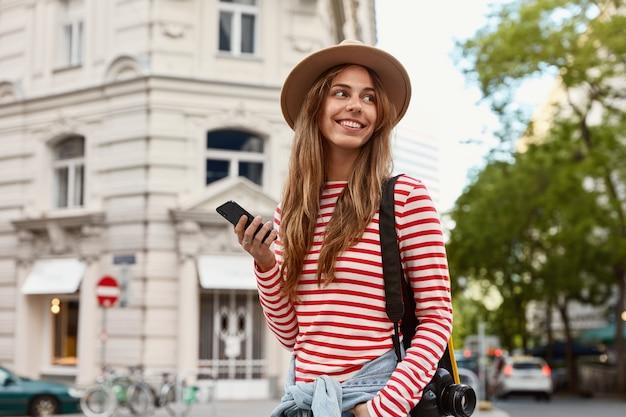 Felice donna viaggiatrice trasporta fotocamera per fare foto, detiene smart phone, messaggi di testo online