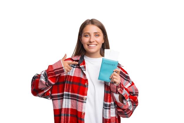 행복한 여성 여행자가 비행기표와 함께 들고 있는 여권을 가리키고 있습니다.