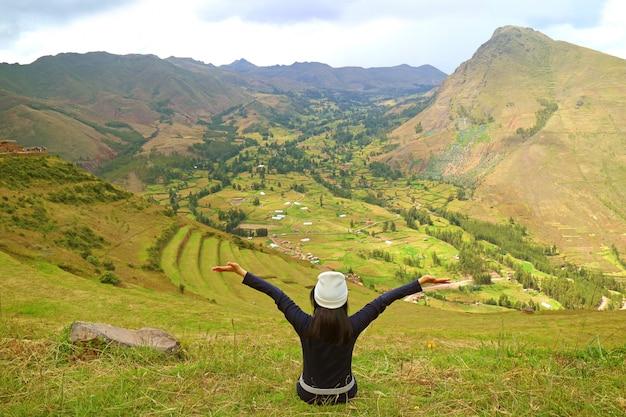 Happy female traveler on the mountain slope of pisac archaeological park, cusco region, peru