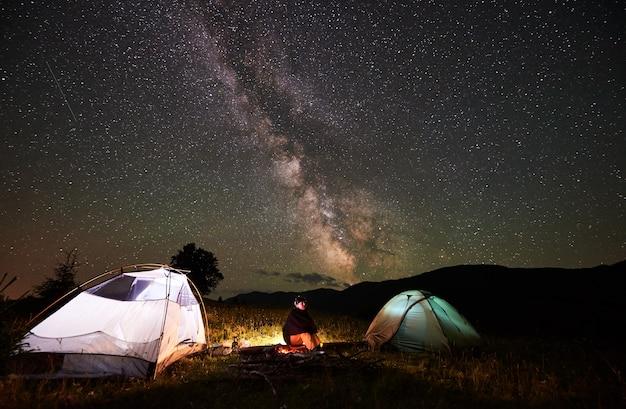 산에서 야영하는 밤에 놀라운 아름다운 별이 빛나는 하늘과 은하수를 즐기는 행복한 여성 여행자. 캠프 파이어 및 두 조명 된 텐트 옆에 로그에 앉아있는 여자.