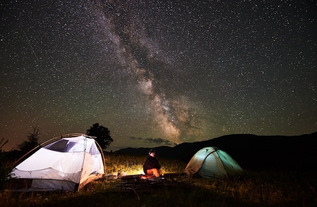 Happy female traveller enjoying incredible beautiful starry sky and milky way at night camping in the mountains. woman sitting on a log beside campfire and two illuminated tents.