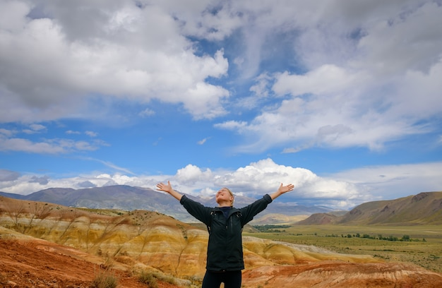 Happy female traveller raising her hands up against the beautiful mountains and blue sky with white clouds on sunny day