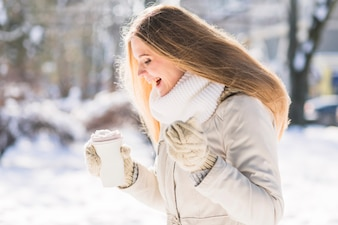 Happy female veterinarian holding takeaway coffee cup standing in snow