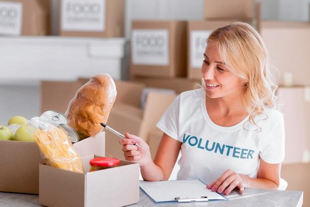 Volontario femminile felice che mette il cibo nelle scatole per la donazione
