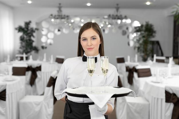 Счастливый женский официант с двумя бокалами белого вина на подносе в ресторане.