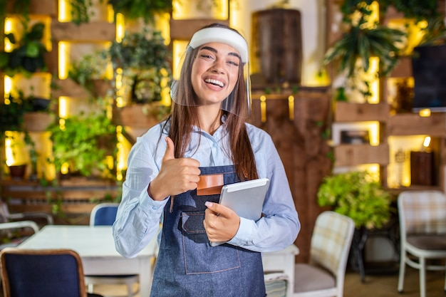 Happy female waitress using digital tablet while wearing visor at the restaurant or cafe. open again after lock down due to outbreak of coronavirus covid-19, new normal