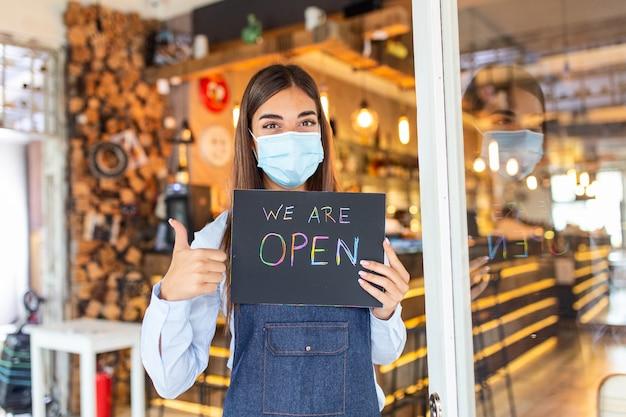 Счастливая официантка с защитной маской, держащая открытую табличку, стоя в дверях кафе или ресторана, снова открылась после блокировки из-за вспышки коронавируса covid-19. показывает знак ок