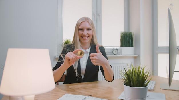 Счастливая женщина с биткойн показывает палец вверх. улыбка веселая белокурая женщина в офисном костюме сидит на рабочем месте с компьютером и показывает биткойн в руке, делая недурно жест