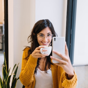 Happy female with cup getting selfiesmiling