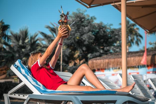 日光の下でサンラウンジャーに横たわっているパイナップルカクテルと幸せな女性