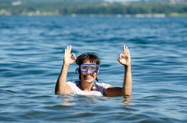 湖の穏やかな水の真ん中で短い髪の幸せな女性