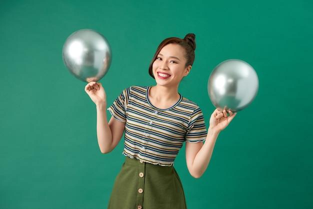 2つの銀の風船を楽しんで、笑顔で幸せな女性。