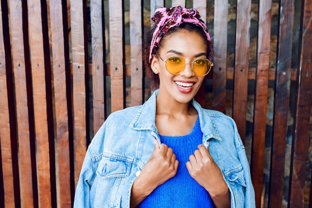 Счастливая женщина со стильными волосами позирует на улице, держа вишневый лимонад, носить джинсовую куртку и синий шерстяной свитер.