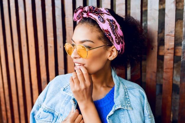 Donna felice con i capelli alla moda in posa all'aperto, tenendo la limonata ciliegia, indossa giacca di jeans e maglione di lana blu.
