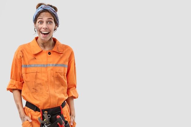 白い壁にポーズをとって幸せな女性労働者