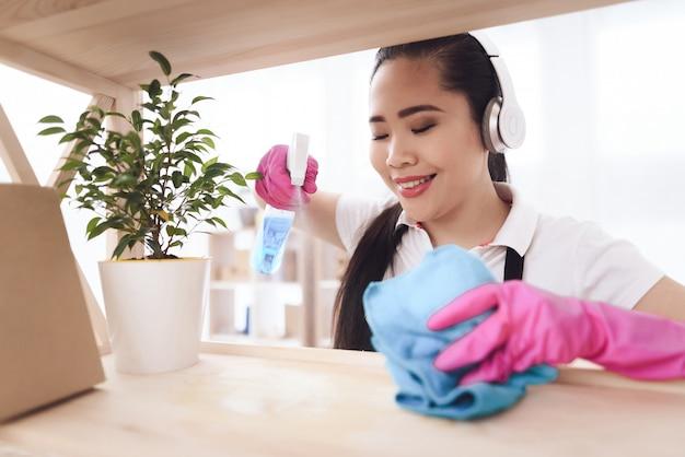 Happy filipino maid cleaning bookshelf in room