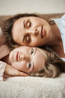 Happy to find soulmate to share her thoughts. vertical shot of attractive blonde girl lying on sofa with her girlfriend lying on her head, smiling broadly, feeling relaxed and cozy at home