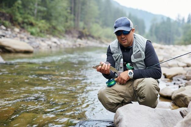 Счастливый рыбак в кепке и солнцезащитных очках, держа в руках форель, сидя у горной реки. зрелый мужчина выглядит довольным уловом. концепция рыболовства.