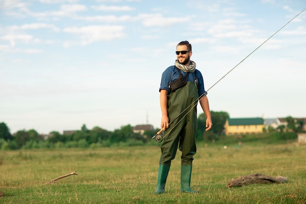 Happy fisherman with special suit and fishing rod