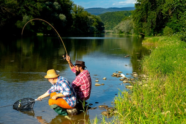 Happy fishermen friendship fishing bearded fisher in water giving your hobby real happiness summer w...