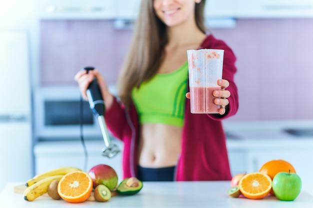 운동복에 맞는 여성은 부엌에서 집에서 핸드 블렌더를 사용하여 신선한 유기농 과일 스무디를 준비합니다.