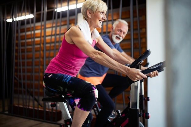 Happy fit mature woman and man cycling on exercise bikes to stay healthy