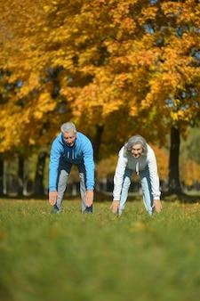 秋の公園で運動する幸せなフィットの年配のカップル