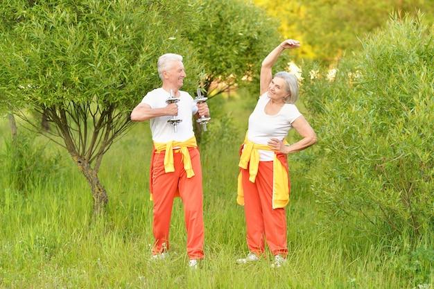 Счастливая пара старших тренируется в парке