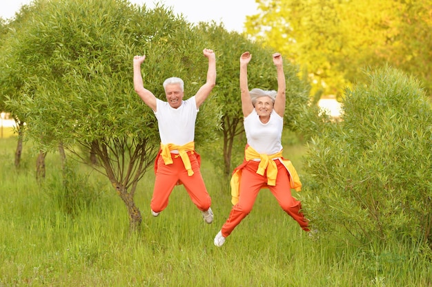 Happy fit senior couple jumping in  park